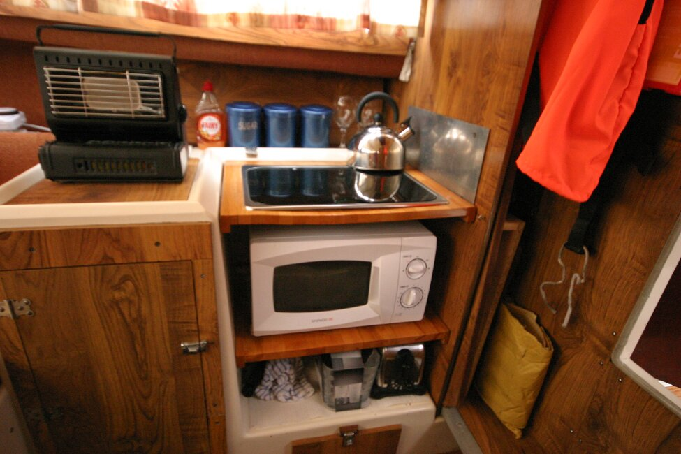 Shetland 640 Hardtopfor sale Galley - Sink, gas hob and microwave. Small portable gas heater on top of sink cover.